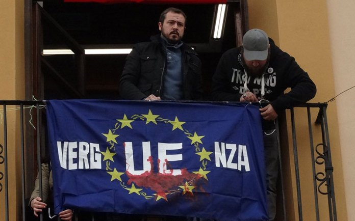 El portavoz de EU, Javier Parra, colocando una bandera de la UE ensangrentada en el balcón del Ayuntamiento