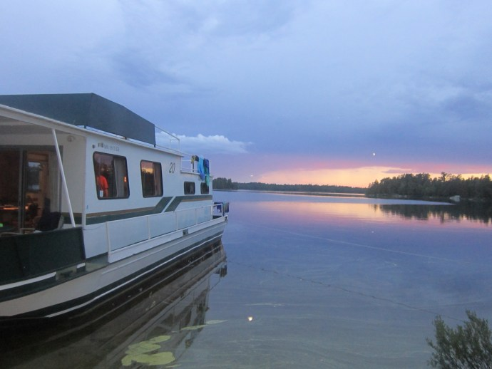 Houseboat on lake with cloudy sunset