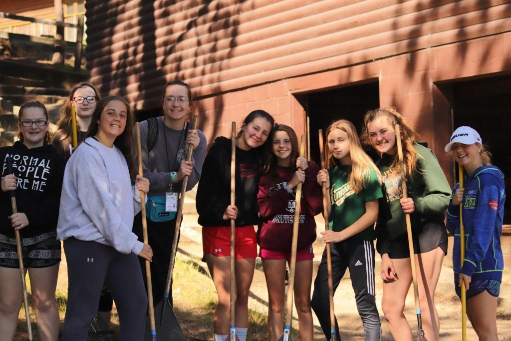 Junior high girls with rakes on path