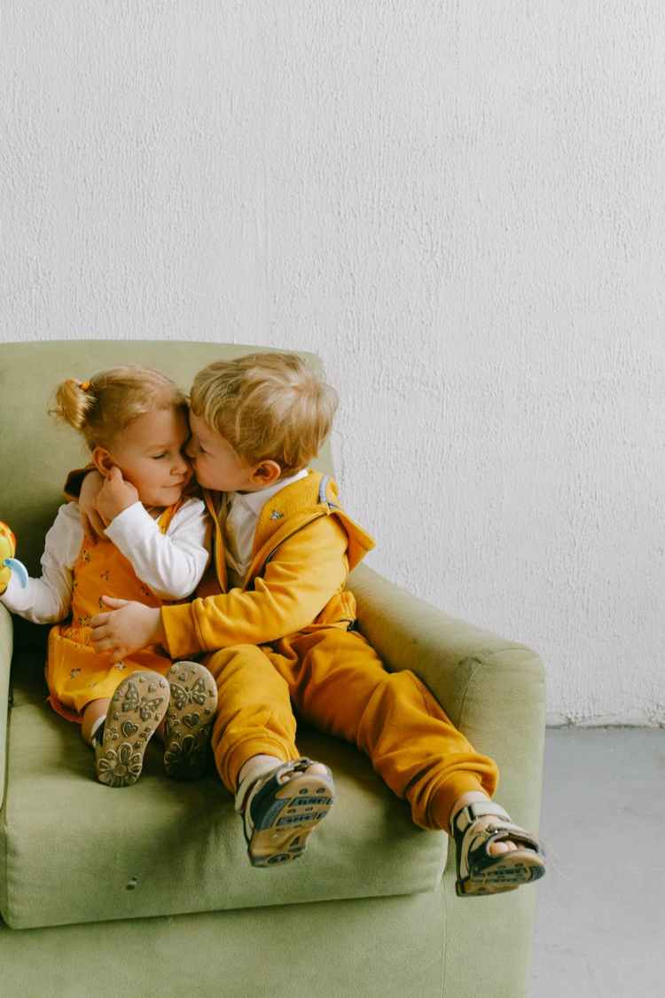 cute children cuddling in armchair at home