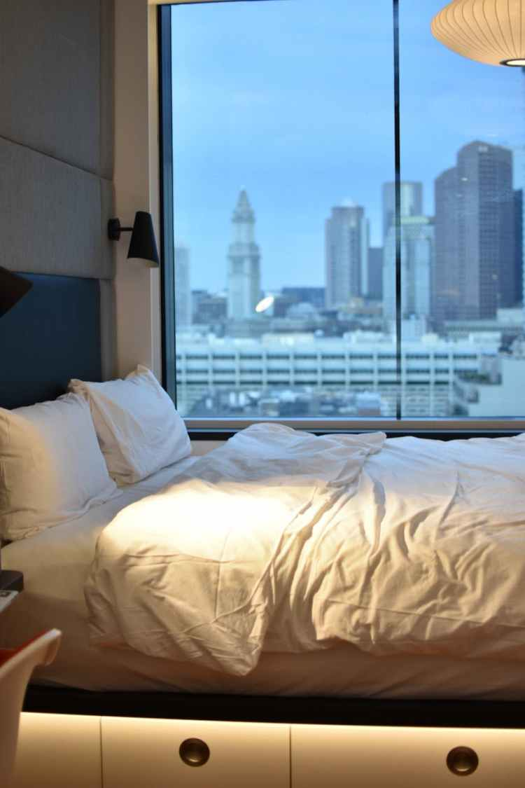 white pillows on bed beside window