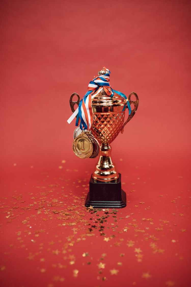 gold and blue trophy on red surface