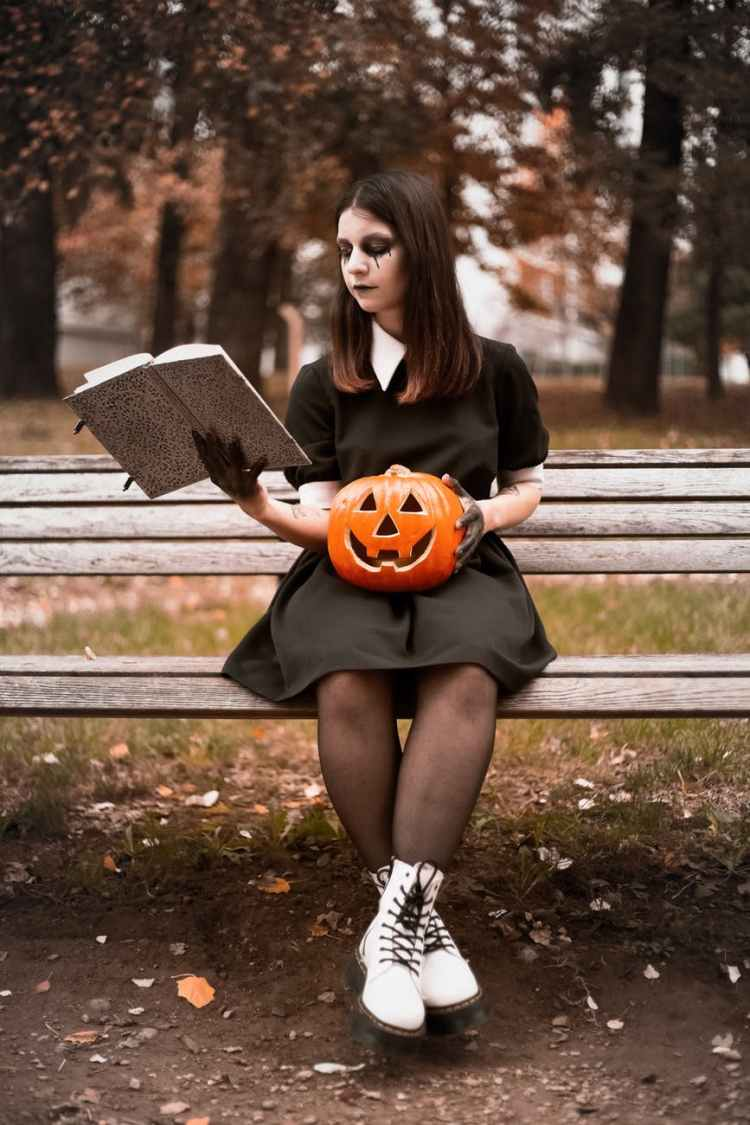 woman in black long sleeve shirt sitting on bench holding jack o lantern