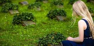 Girl kneeling at grave