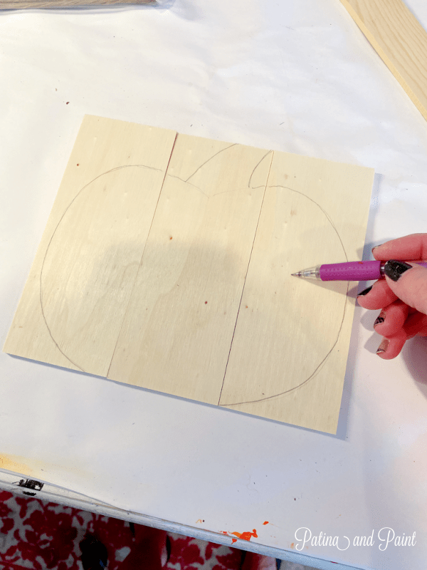 drawing a pumpkin on wooden pieces
