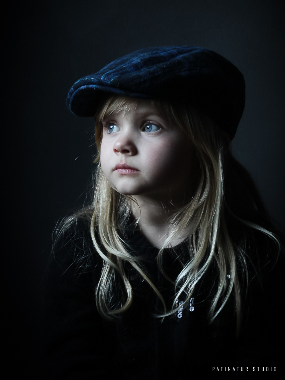 Chiaroscuro portrait of a little girl with a blue flat cap