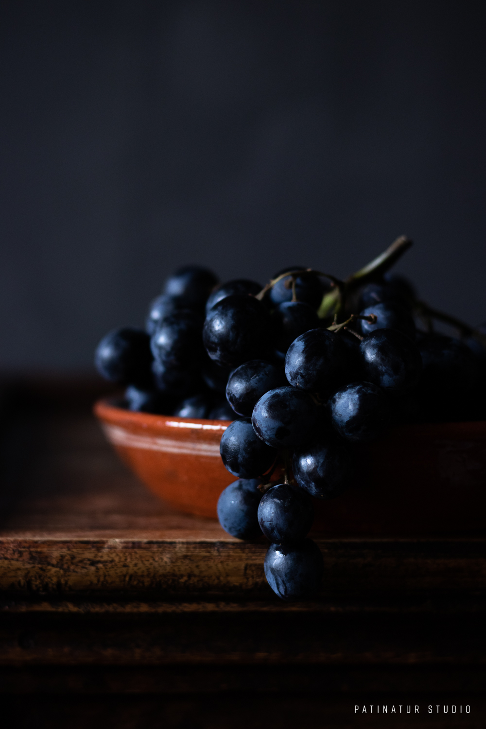 Photo art | Dark and moody still life with grapes in rustic terracotta bowl