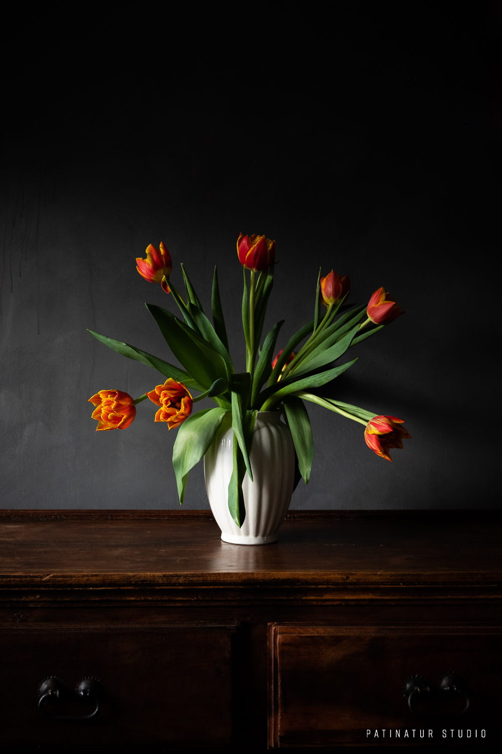 Photo art | Dark and moody still life with red and yellow tulips in white ceramic vase