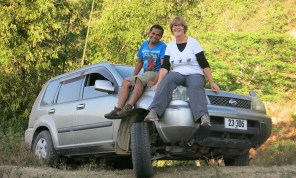 Abrau and Liz provide ballast on the front right while the locals help push the car back on the road.