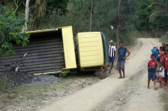 A truck carrying a load of gravel has slipped off the steep dirt road and toppled into the ditch. The driver and a child are unharmed but the truck's lying on its side like a beached whale.