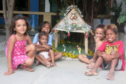 Kids from our family compound gather round a mini Prezepiu (Nativity scene) in our front yard.