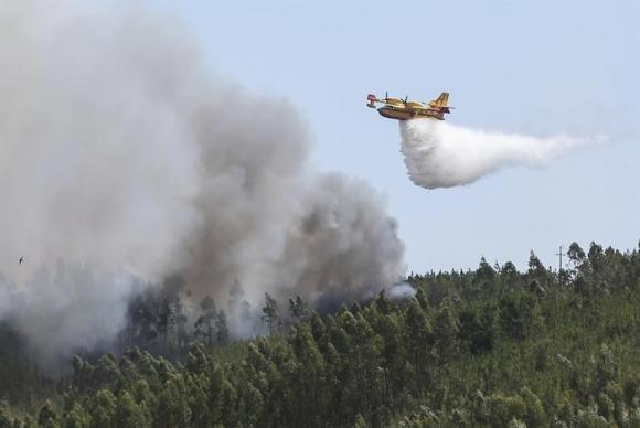 Um avião é usado pelos bombeiros para ajudar no trabalho de extinção de um incêndio em Carreira do Mato, Abrantes, no centro de Portugal