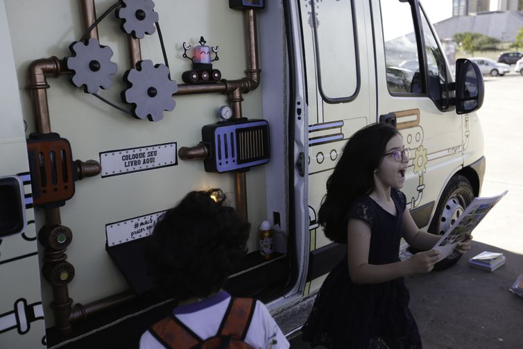 """Van """"Máquina de livros"""" faz troca de livros no Museu da República, em Brasília. Da máquina, saem capas coloridas, obras ilustradas, literatura de todos os tipos. É possível escolher entre obras para crianças ou para pessoas mais velhas."""