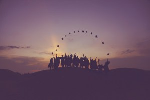 graduates throwing hats in sky