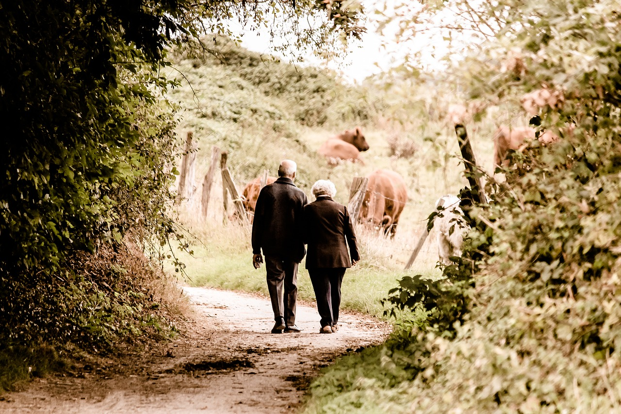 elderly couple walking down path together