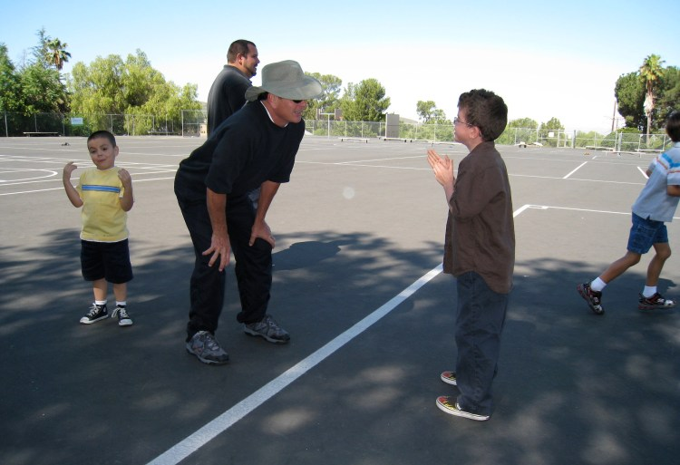Nine year old Dylan Harvey speaks with his adaptive physical education teacher during class.