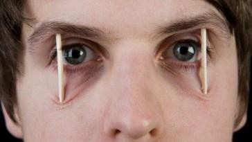 Pessoa com palitinhos nos olhos - Turbine o Desempenho Mental e Afaste o Cansaço!
