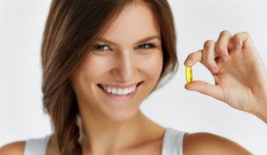 Nutrition. Healthy Lifestyle. Close Up Of Happy Woman Holding Pill With Cod Liver Oil Omega-3. Medicine, Nutritional Supplements. Sport, Beauty And Diet Concept. Vitamin D, E, A Fish Oil Capsules.