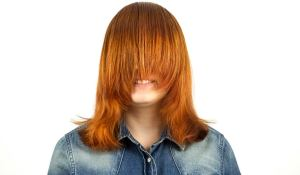 Smiling redhead teenage girl with a haircut that hides her face