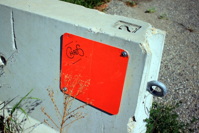 CHAOS written on an orange reflector square screwed to a concrete bollard