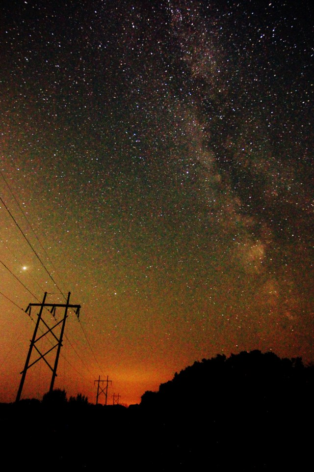 The Milky Way above the road and trees