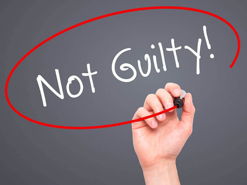 """Justification by grace with a writing on a black board stating """"not guilty"""""""