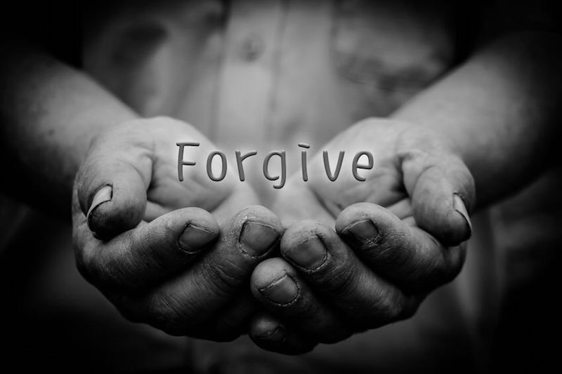 The power to forgiven showing the word forgiveness written with a man's hands under