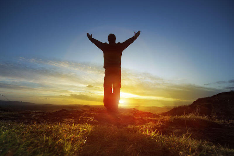 True worshippers image showing a man worshipping the Lord with hands lifted up