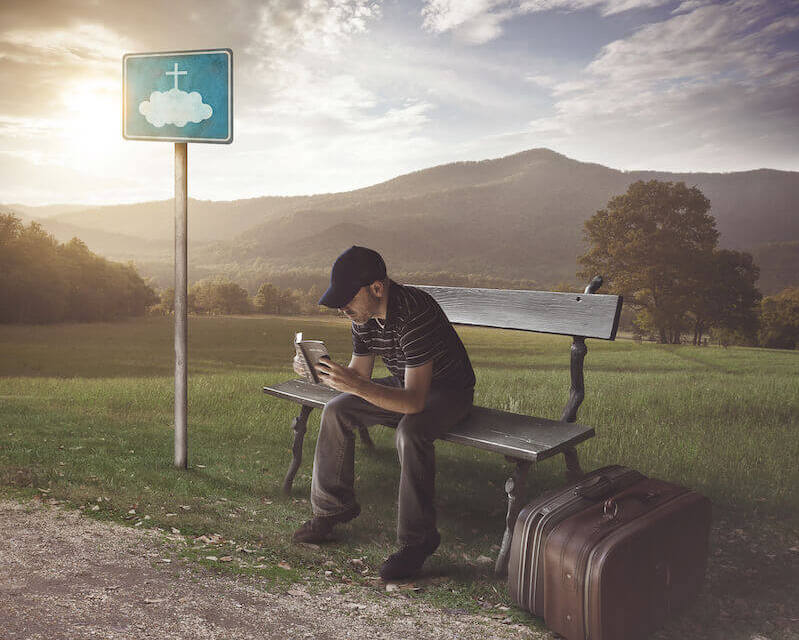 A man waiting at a bus stop reading the Bible