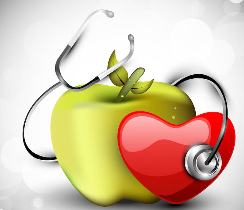 good health image showing an apple , stethoscope and a heart