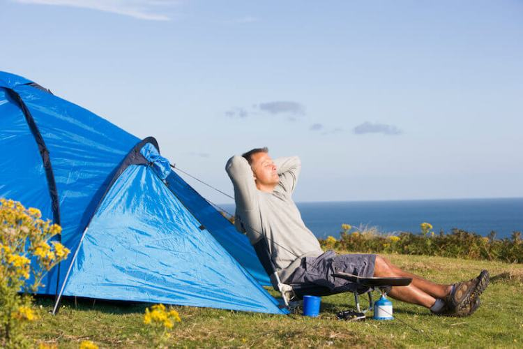 Enlarge the place of thy tent and showing a man camping outdoors
