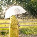 a woman in yellow rain coat under the rain