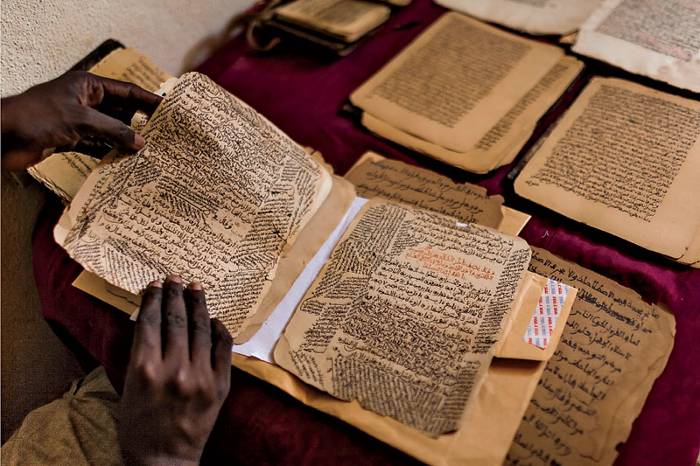 Malian calligrapher Boubacar Sadeck consults an ancient manuscript at his home in Bamako, Mali.   <em>Photo</em>: Marco Di Lauro/Reportage by Getty Images