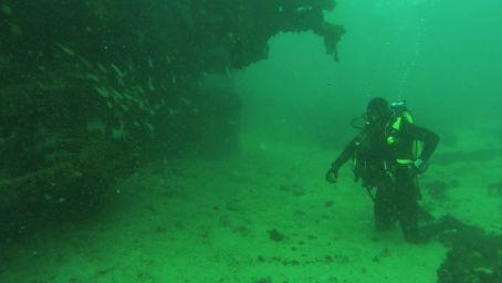 Un submarinista de la Armada junto al pecio de una embarcación.