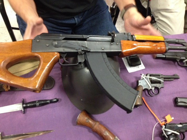 A picture of a seller holding an AK-47 at a gun show.