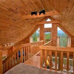 A vaulted ceiling with large windows and stuffed bears on a beam inside a cabin.