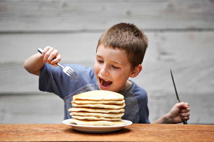 Boy enthusiastically getting ready to eat a large stack of pancakes