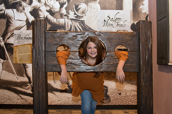 A girl smiles with head head and arms in a pillory display at a museum