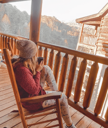 A woman sits in a rocking chair on a cabin porch