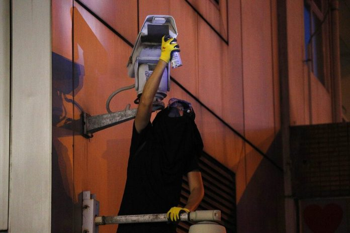 A protester spray paints the view of the surveillance camera outside the Chinese Liaison Office in Hong Kong, Sunday, July 21, 2019. Protesters in Hong Kong pressed on Sunday past the designated end point for a march in which tens of thousands repeated demands for direct elections in the Chinese territory and an independent investigation into police tactics used in previous demonstrations. Photo: Bobby Yip / AP