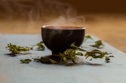 A simple mug with no handle sits on a gray cloth surface against a warm brown background. The mug is black with a burnt orange interior just visible along the top, almost obscured by the steam rising from the drink inside. Dried green herbs are scattered around the mug.