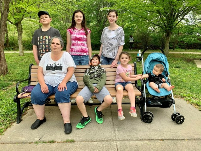 Patty Fletcher sits on a wooden bench in a park surrounded by her six grandchildren, one of whom is sitting in a blue stroller on the right of the bench. Two of her grandchildren are sitting on the bench alongside Patty and the other three are standing up behind it. The trees and grass in the park are a luscious green color.