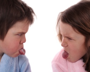 photo of a boy and girl sticking their tongues out at each other