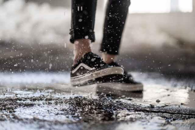 crop person walking through puddles on asphalt