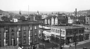 THEN: The scene looks north through a skyline of steeples toward the Cascade neighborhood and Lake Union, ca. 1923.
