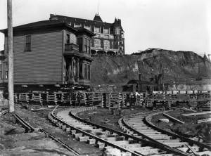 THEN: An early-20th-century scene during the Second Avenue Regrade looks east into its intersection with Virginia Avenue. A home is being moved from harm's way, but the hotel on the hill behind it would not survive the regrade's spoiling. Courtesy of Ron Edge.