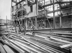 THEN: Steel beams clutter a freshly regraded Second Avenue during the 1907 construction of the Moore Theatre. The view looks north toward Virginia Street.