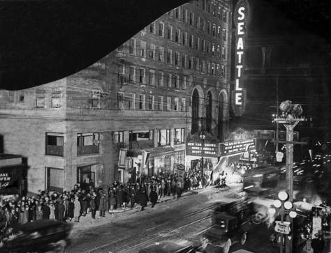 "THEN: As explained in the accompanying story the cut corner in this search-lighted photo of the ""first-nighters"" lined up for the March 1, 1928 opening of the Seattle Theatre at 9th and Pine was intended. Courtesy Ron Phillips"