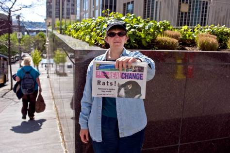 NOW: Appropriately, for the contemporary repeat Jean Sherrard recorded Cassie Phillips, a Real Change newspaper salesperson, showing her fare at the same corner.