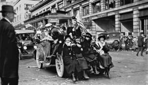 """THEN: With feet nearly touching the Madison Street Cable Railway's cable slot, five """"happy workers"""" squeeze on to the front bumper of an improvised Armistice Day float. (Photo courtesy Grace McAdams)"""